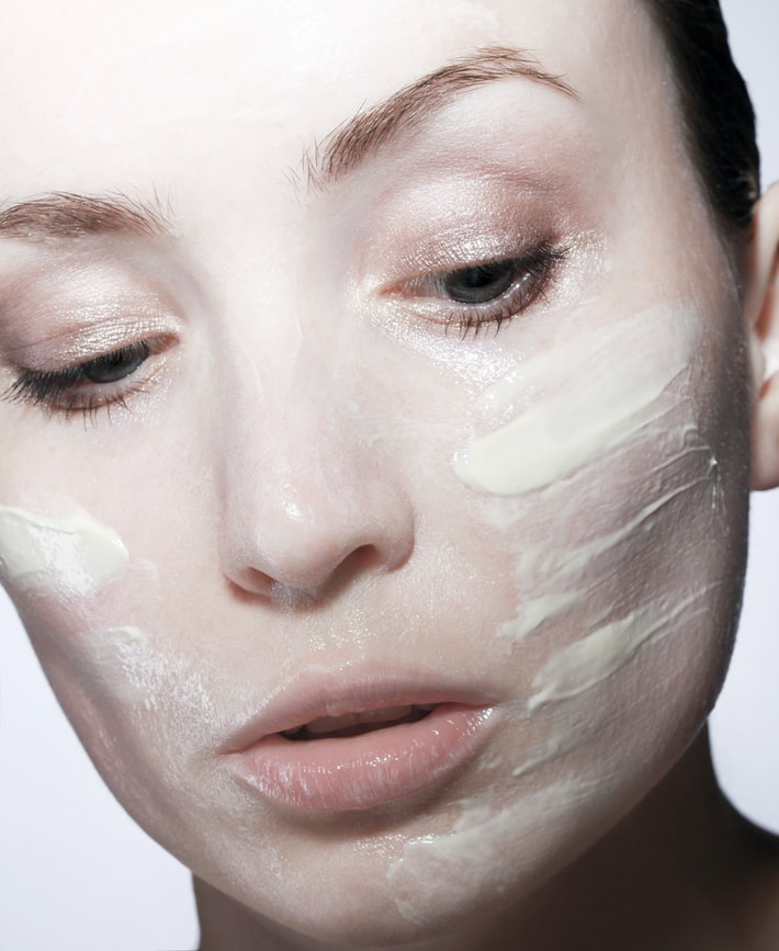 woman with white facial mask cream applied on her cheeks